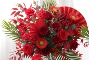 Red roses gerberas carnations with golden cane palm leaves tropical foliage in basket arrangement