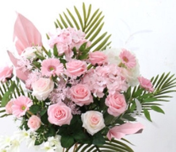 Pink roses gerberas carnations with areca palm leaves in basket arrangement