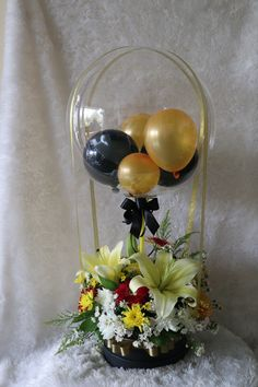 Clear Balloon with 2 black 2 Gold balloons inside with 3 white Lilies and 10 White Red Carnations Basket