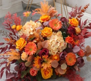 Orange roses gerberas carnations golden cane palm leaves tropical foliage in basket arrangement